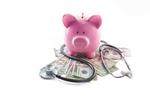 Piggy bank on stethoscope w pile of money